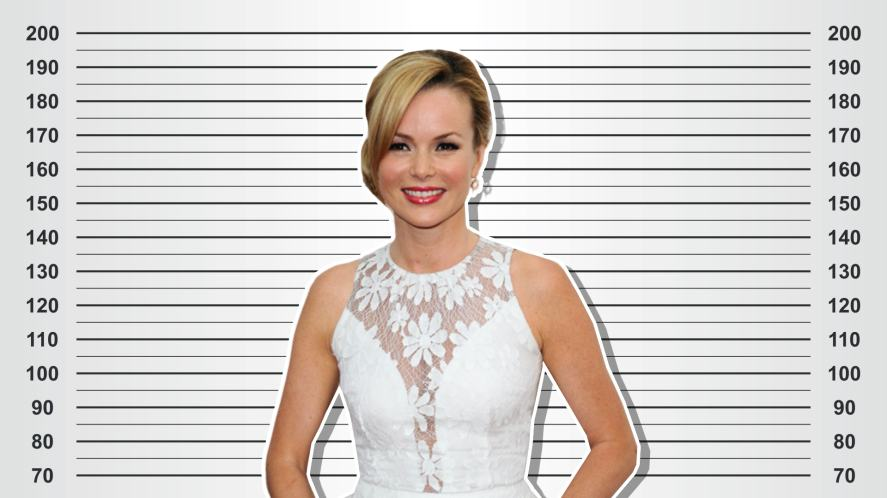 Amanda Holden in a white dress against a height chart