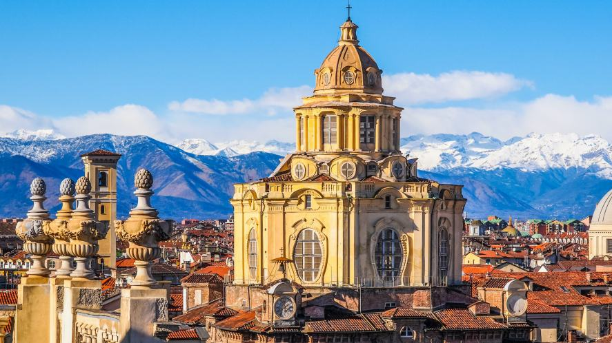 An Italian city with snowy mountains in the background