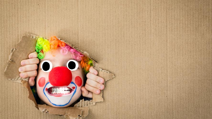 A clown peeking out of a cupboard