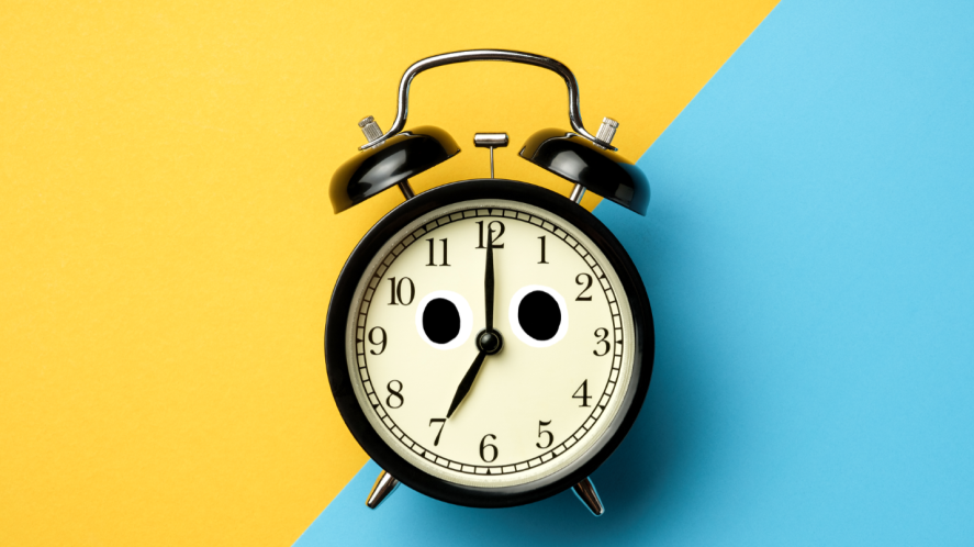 Alarm clock on yellow and blue background