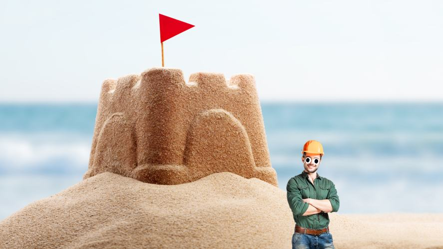 A big sandcastle and construction worker