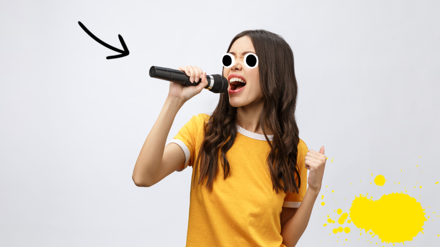 Woman singing into microphone on grey background