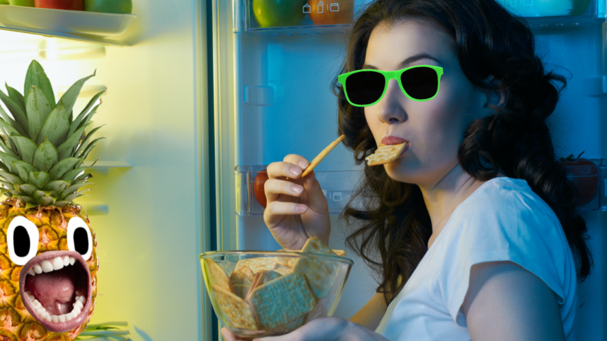 A person eating a snack from a fridge