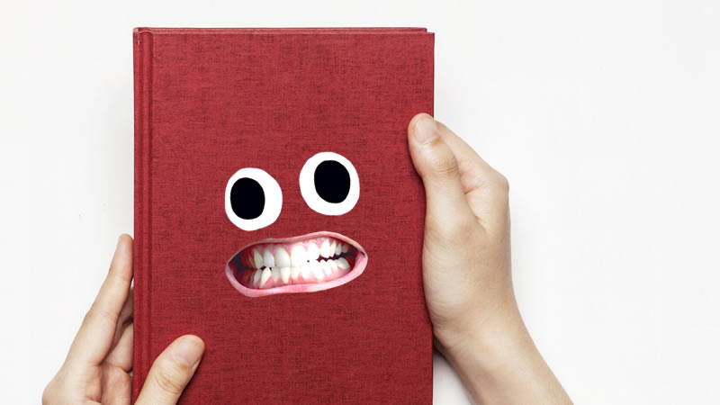 A person holding a grinning red book