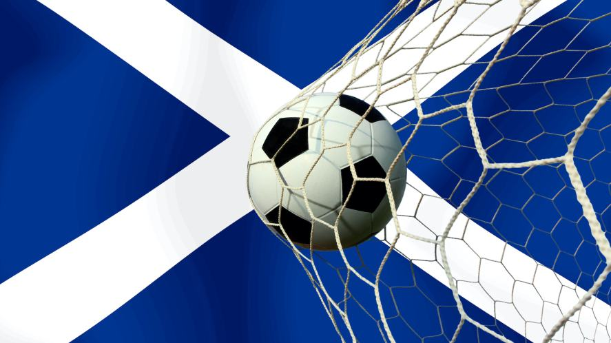 a football bursting the net in front of a Scottish flag