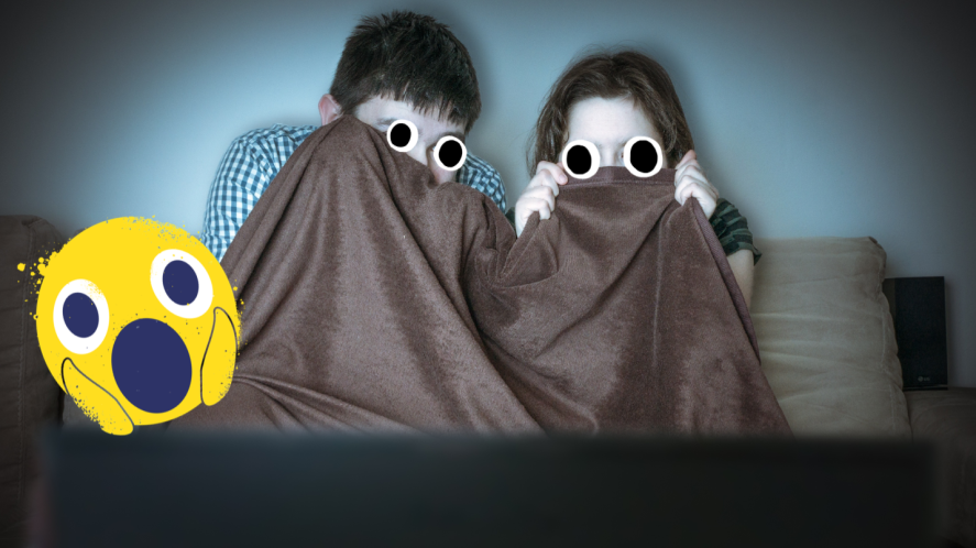 Two children hiding under a blanket looking scared