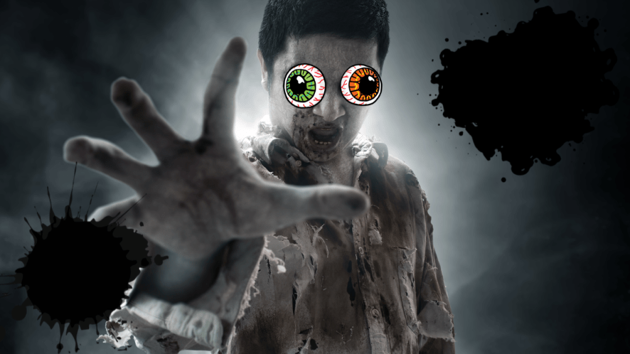 Zombie reaching hand out on grey background