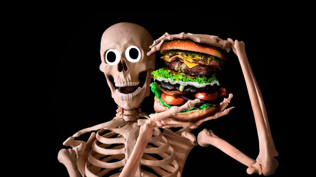 Laughing skeleton holding a huge hamburger
