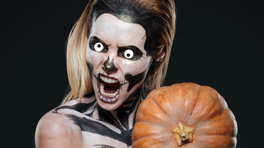 Girl with scary skeleton makeup and pumpkin