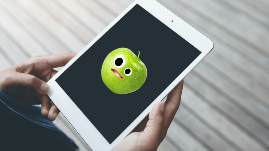 An iPad with an actual apple on the screen