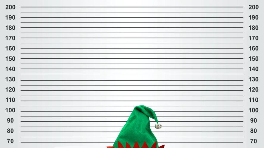 An elf standing next to a wall chart