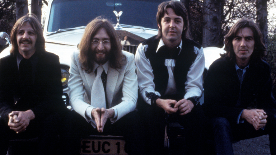 The Beatles sitting on a car