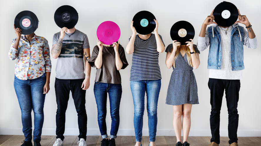 A line of people holding records up to their faces