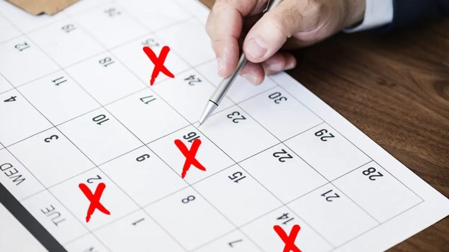 A person marking important dates on their wall calendar